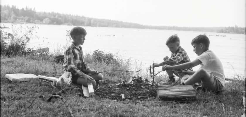 Drie jongens zitten in de jaren vijftig rond kampvuur aan het water