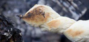 Een broodje op een stok boven open vuur gebakken buiten Oudersvannature.nl