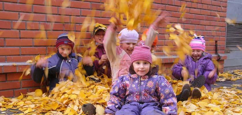 kinderen spelen met bladeren