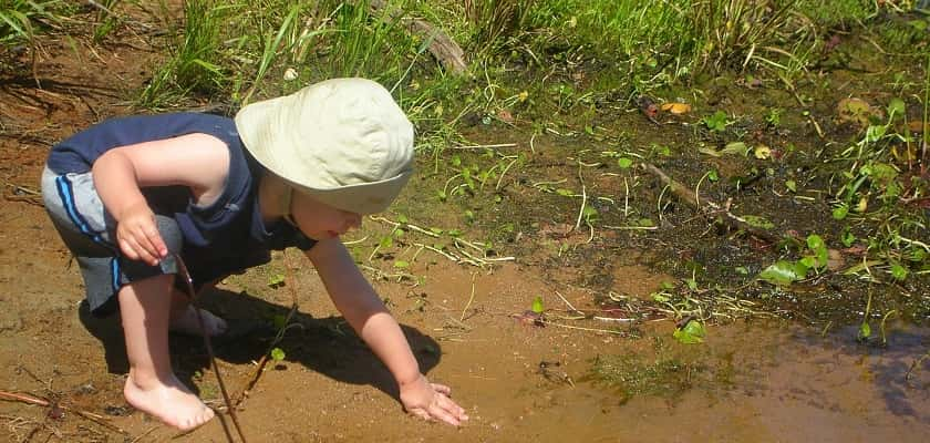 peuter speelt bij modderplas